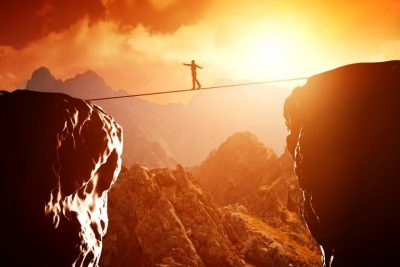 Man walking a tight rope between two mountains as the Global economy tries to balance