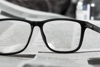 Reading glasses placed on a newspaper reporting equity release rate increase and rural properties in high demand after lockdown