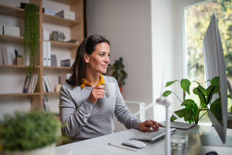 Lady working at kitchen table on laptop, multi-tasking with additional work