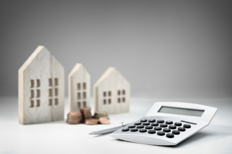 Models of houses alongside calculator and cash, working out equity release